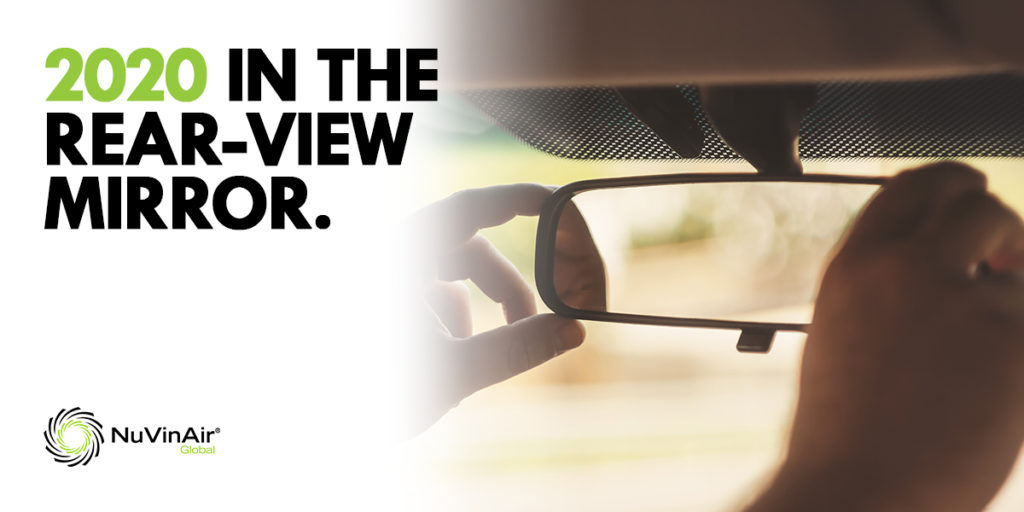 2020 in the rear-view mirror. Image of hand adjusting rearview mirror inside a vehicle.